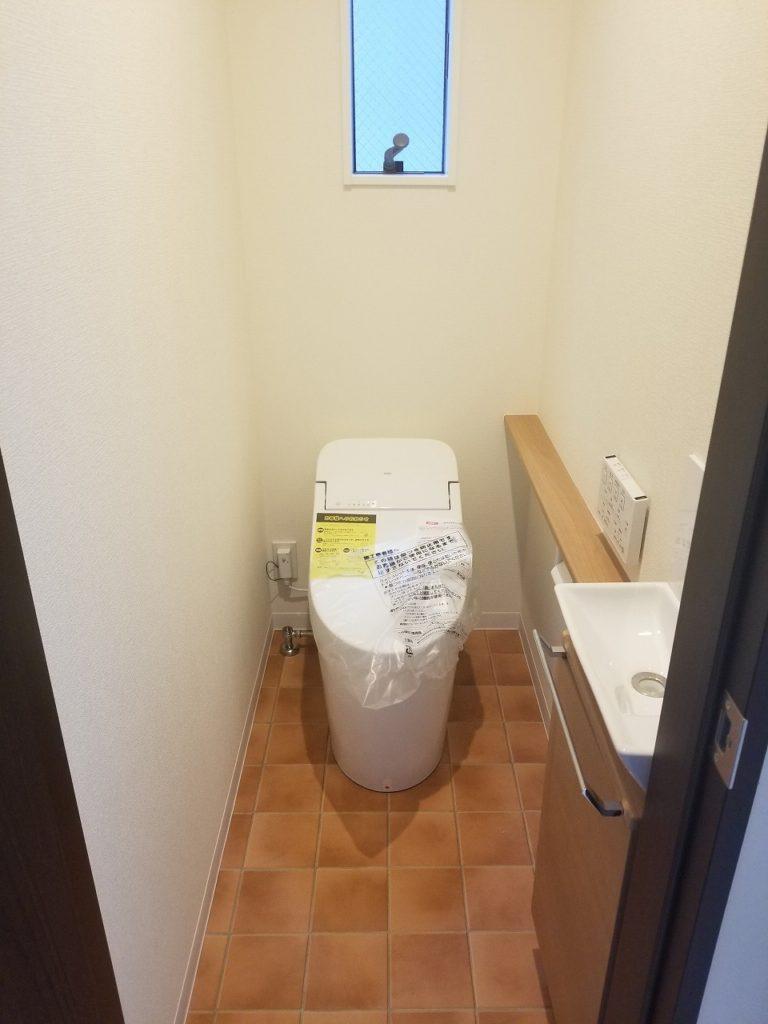 タンクレスでスッキリとした印象の温水洗浄付きトイレ。テラコッタカラーの床でヨーロッパ風に。。